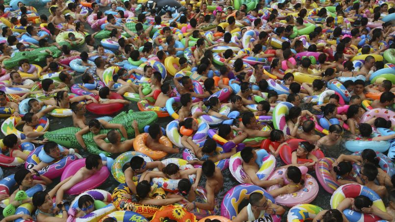 Visitors crowd an artificial wave pool at a tourist resort to escape the summer heat in Daying county of Suining